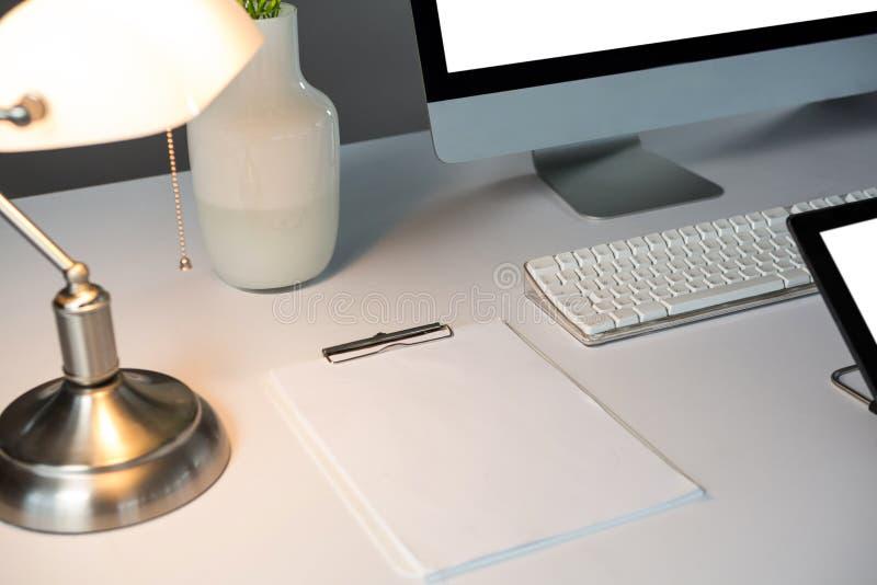 Komputer stacjonarny i stołowa lampa z pustego papieru prześcieradłami, zdjęcie royalty free