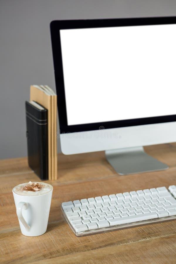 Komputer stacjonarny z filiżanką kawy i dzienniczkiem fotografia stock