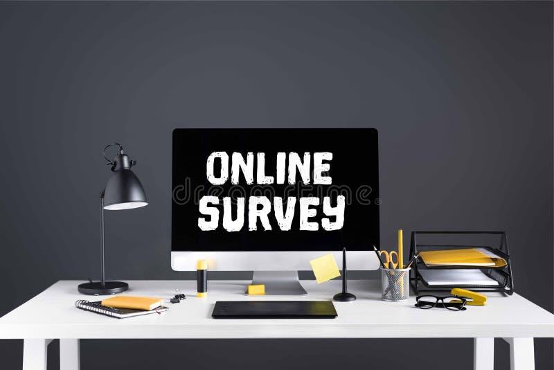 komputer stacjonarny z online ankiety inskrypcją na ekranie, grafiki pastylce i biurowych dostawach, obraz royalty free