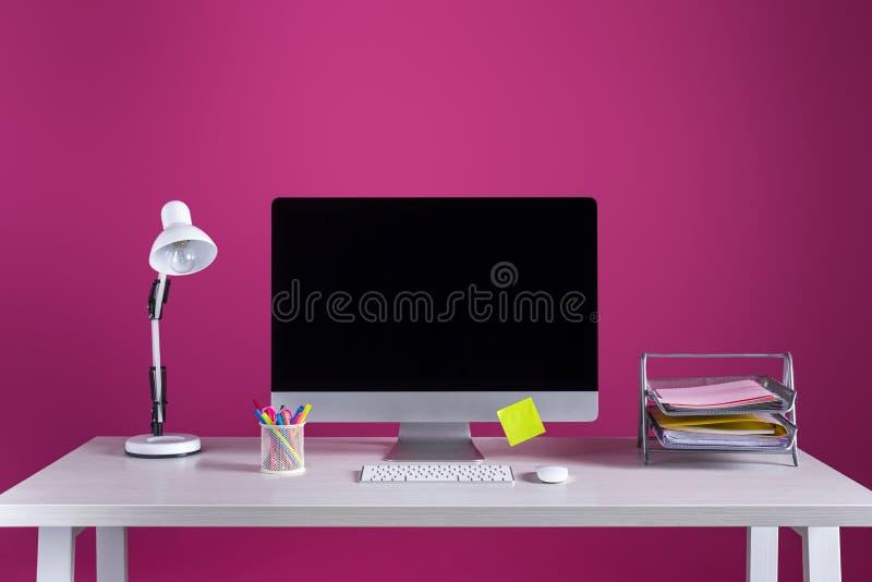 Komputer stacjonarny z pustym ekranem, biurowymi dostawami i lampą na stole, obraz royalty free