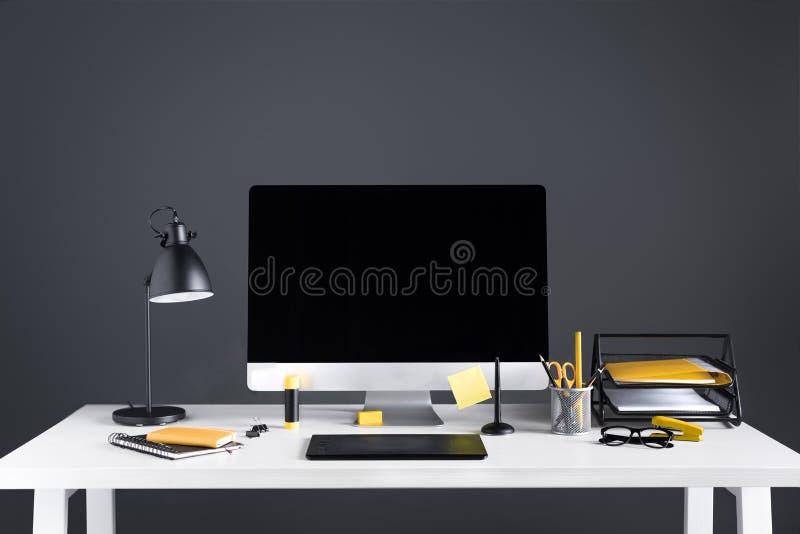 Komputer stacjonarny z pustym ekranem, grafiki pastylką i biurowymi dostawami, zdjęcia stock
