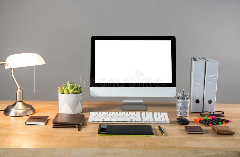 Komputer stacjonarny z stołową lampą i biuro materiały fotografia stock