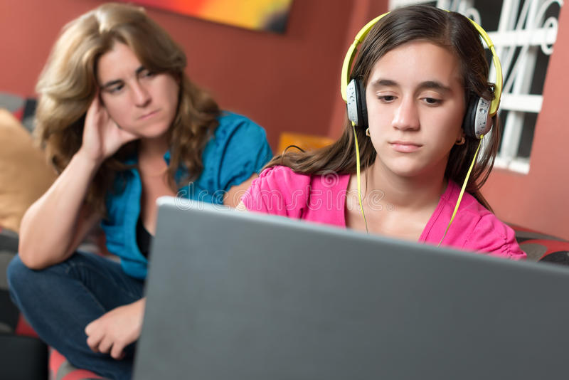 Komputer uzależniająca się dziewczyna ignoruje jej zmartwionej matki obraz stock