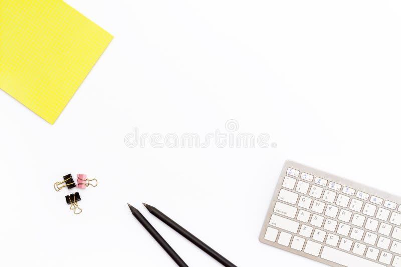 Komputerowa klawiatura, żółty ochraniacz, dwa czarny ołówek i klamerki dla papieru na białym tle, Minimalny biznesowy pojęcie biu zdjęcia stock