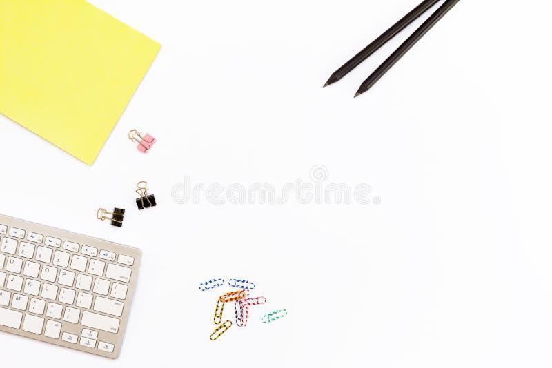 Komputerowa klawiatura, żółty ochraniacz, dwa czarny ołówek i klamerki dla papieru na białym tle, Minimalny pojęcia miejsce pracy obrazy royalty free