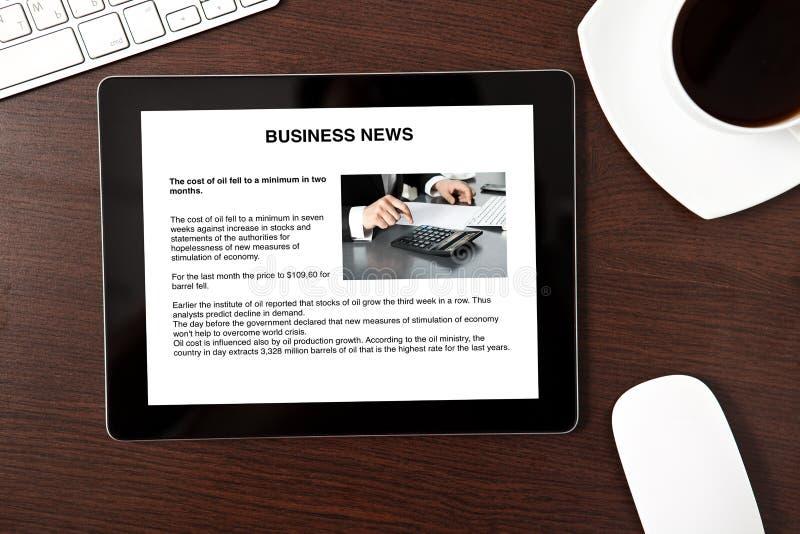 Komputerowa pastylka jest na stole z wiadomości gospodarcze na ekranie zdjęcia royalty free