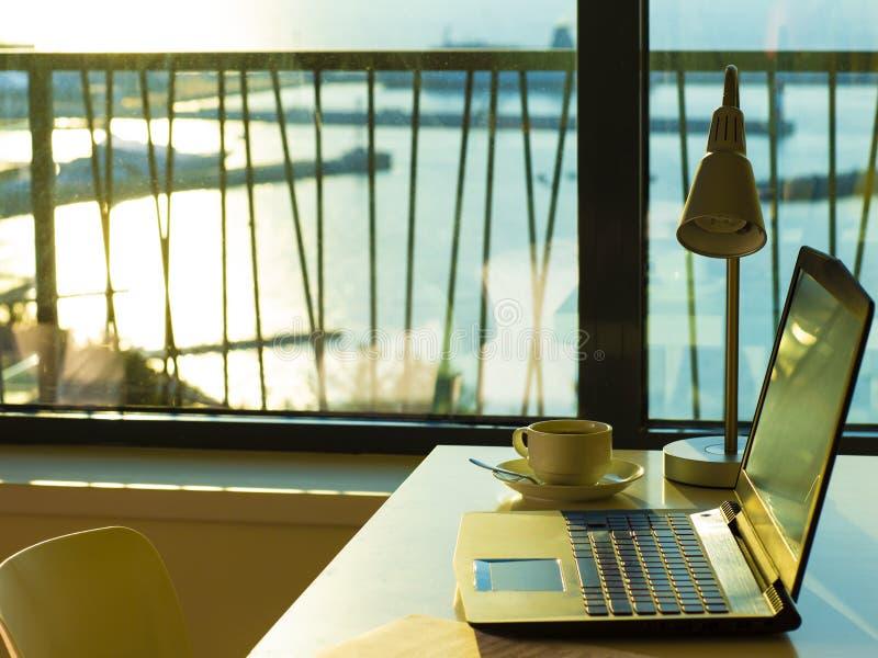 Komputerowy laptop i filiżanka kawy na stołu inside nowożytnym pokoju zdjęcia royalty free