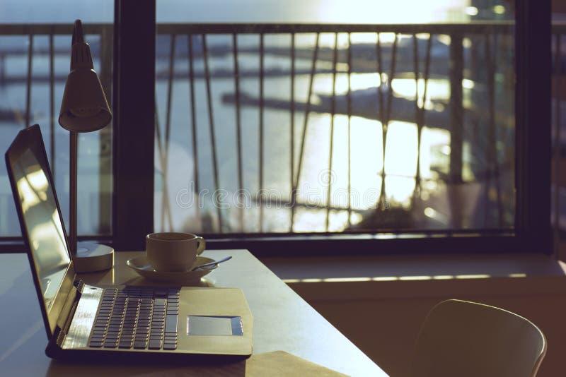 Komputerowy laptop i filiżanka kawy na stołu inside nowożytnym pokoju który lokalizował zakończenie denna plaża, zdjęcie royalty free