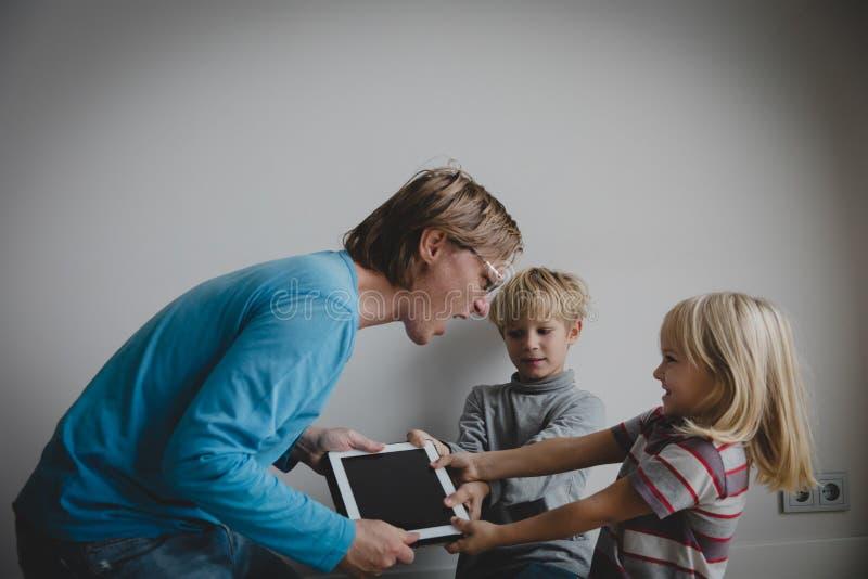 Komputerowy nałogu ojciec bierze dotyka ochraniacza od gniewnych dzieciaków zdjęcie stock