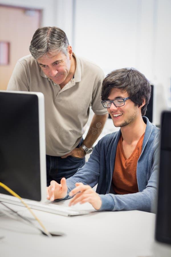 Komputerowy nauczyciel pomaga ucznia zdjęcia stock