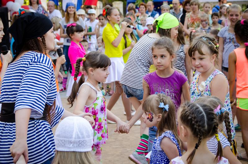 Girl dressed in a pirate costume leads roundelay with group of children stock photography