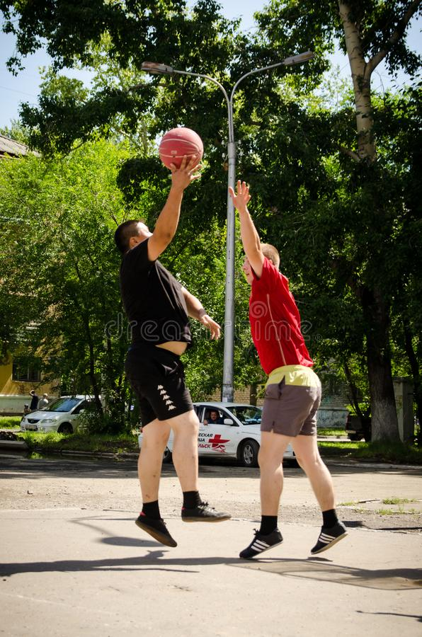 Young men play amateur basketball in summer. Low point shooting stock image