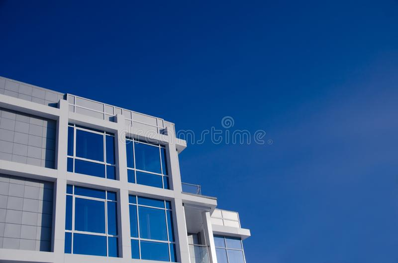 Modern business building with large mirrored windows against blue sky stock image