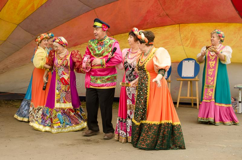 Artists in bright festive Russian national costumes sing folk songs royalty free stock photo