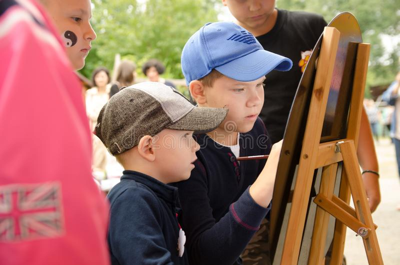Boy draws a pencil participates in a competition for the market royalty free stock image