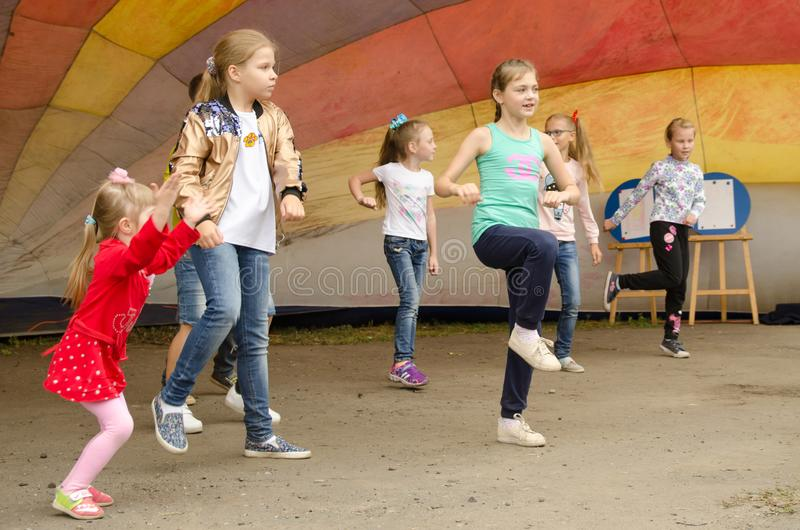 Children have fun dancing under a multi-colored tension dome at a city fair royalty free stock photo