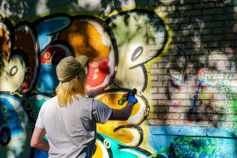 Draws graffiti on a brick wall royalty free stock photo