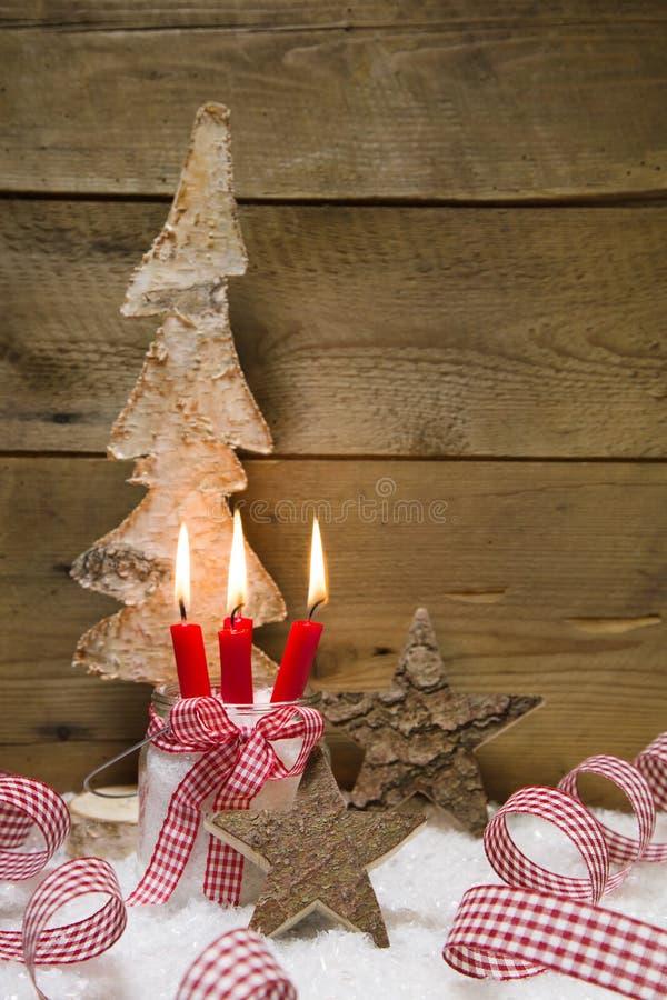 Komst: drie rode brandende kaarsen met Kerstmisdecoratie royalty-vrije stock foto