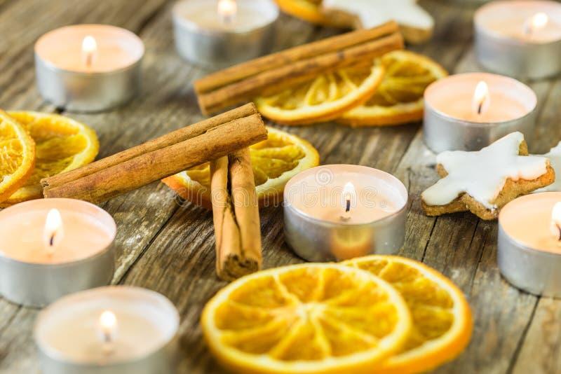 Komst en Kerstmisdecoratie met het branden van kaarsen, oranje plakken, kaneel en sterkoekjes royalty-vrije stock afbeelding