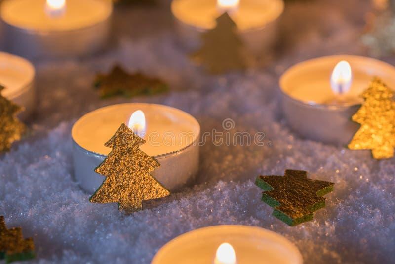 Komst en Kerstmiskaarsen met gouden Kerstmisbomen op sneeuw bij nacht royalty-vrije stock afbeeldingen