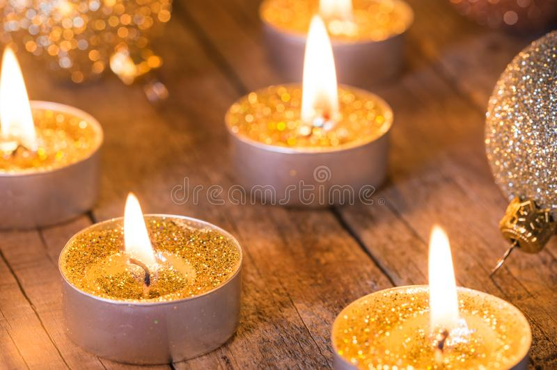 Komst en Kerstmiskaarslichten met gouden fonkelende ballen stock foto