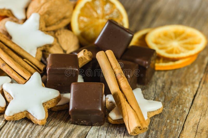 Komst en Kerstmisvoedsel, chocolade, sterkoekjes, kaneel, noten en oranje plakken stock foto's