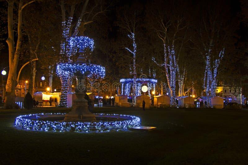 Komst in het park van Zagreb - Zrinjevac-door Kerstmislichten dat wordt verfraaid stock afbeeldingen