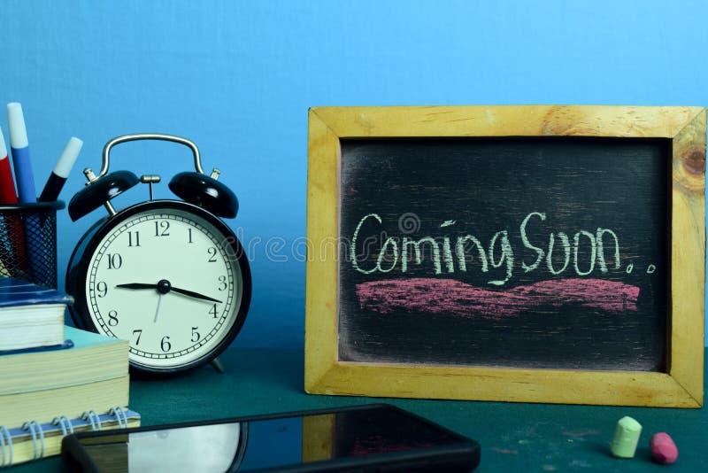 Komst spoedig Plannend op Achtergrond van Werkende Lijst met Bureaulevering stock foto's