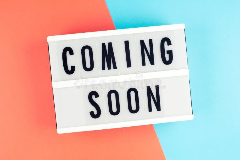 Komst spoedig - tekst op een vertoning lightbox op blauwe en rode helder stock afbeelding