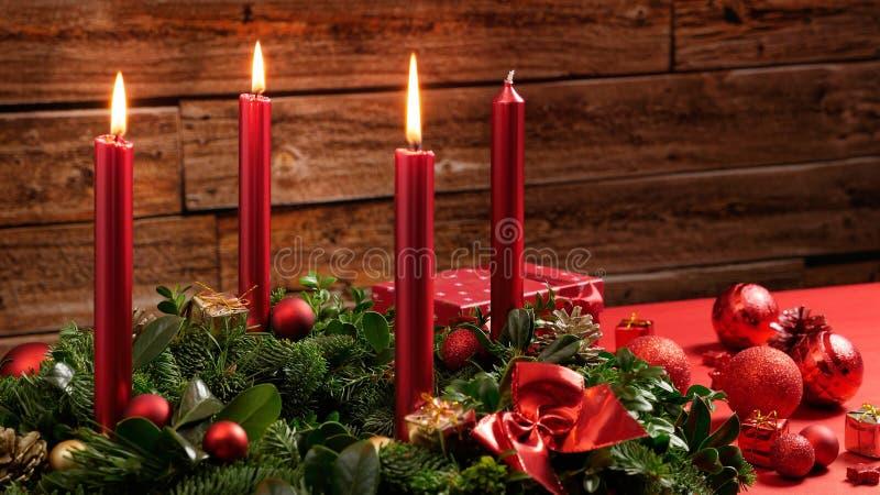 Komstkroon met drie brandende kaarsen en feestelijke decoratie voor een uitstekende houten muur stock afbeelding