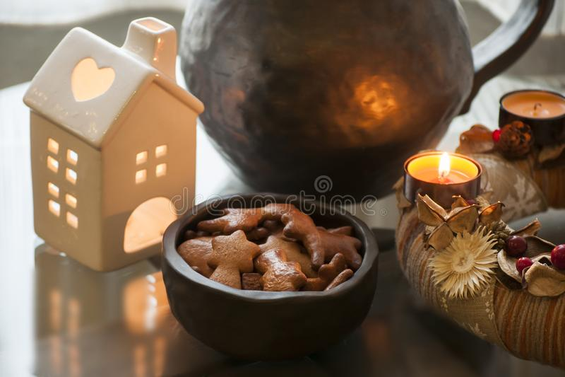Komstkroon met het branden van kaars en heerlijke eigengemaakte peperkoekkoekjes in kleine kom zwart aardewerk stock foto