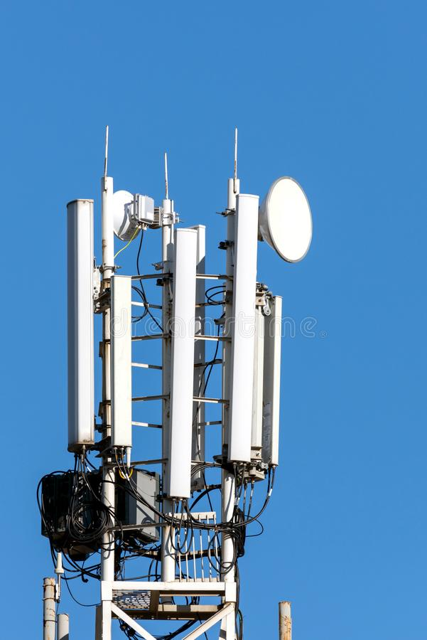 Komunikacyjny telefonu komórkowego wierza na niebieskiego nieba tle zdjęcie stock