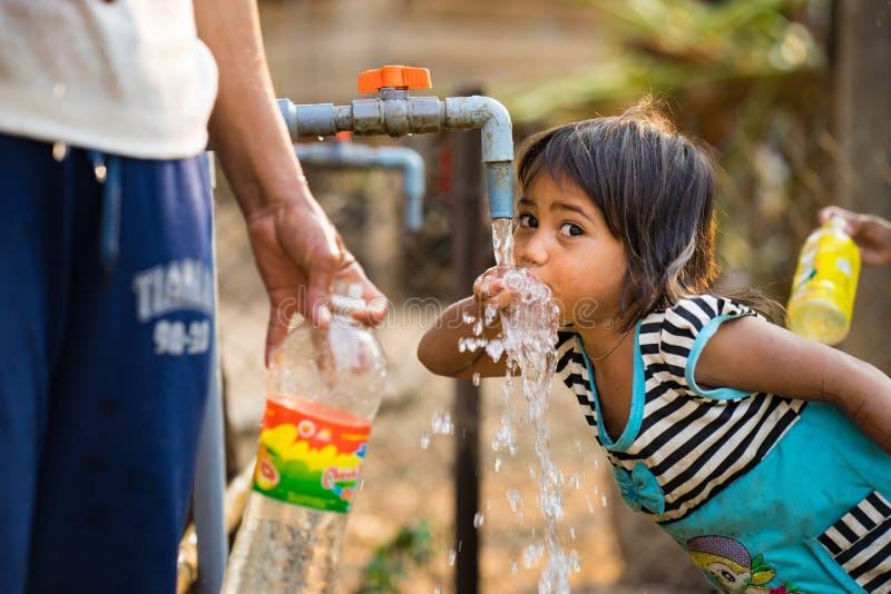 Kon Tum, Vietnam - breng 29, 2016 in de war: Een klein meisje drinkt water van openluchtkraan die watervoorziening door boringspu royalty-vrije stock foto