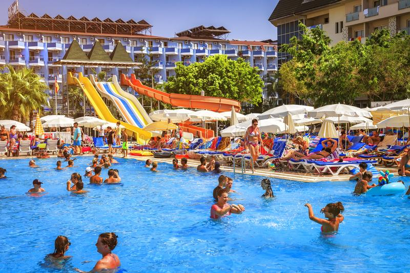 Konakli, Turkey - August 18, 2017: Swimming pool with water park in resort tropical hotel. Happy people swim and relax in pool royalty free stock photo