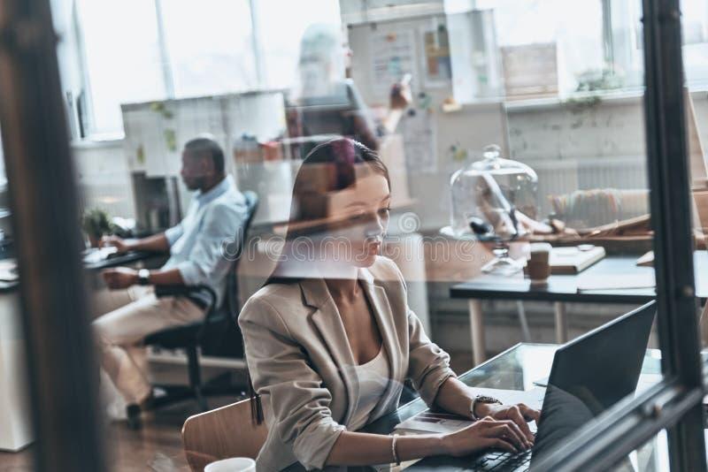 koncentration full Bästa sikt av den moderna unga kvinnan som använder compute arkivbild