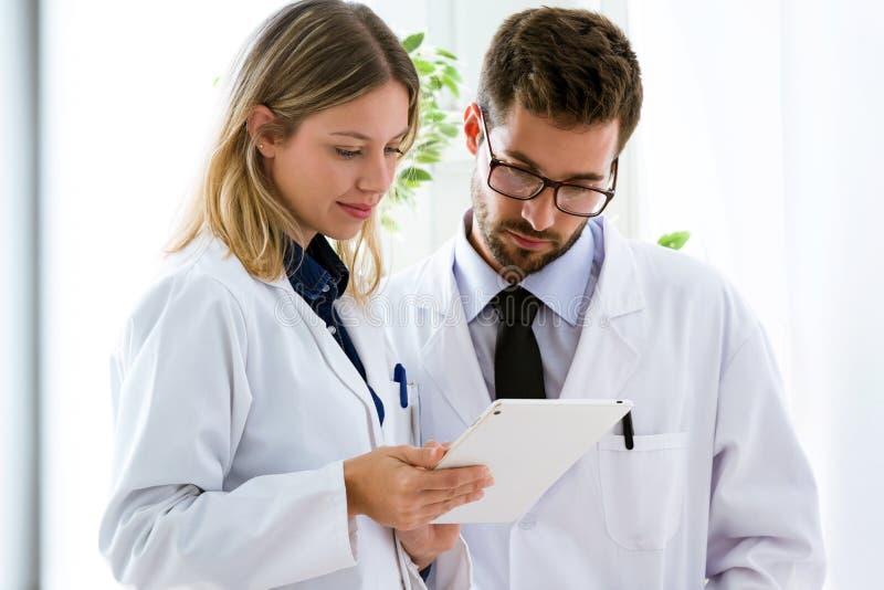 Koncentrera unga säkra doktorer som ser medicinska rapporter i digital minnestavla i medicinskt kontor arkivfoton
