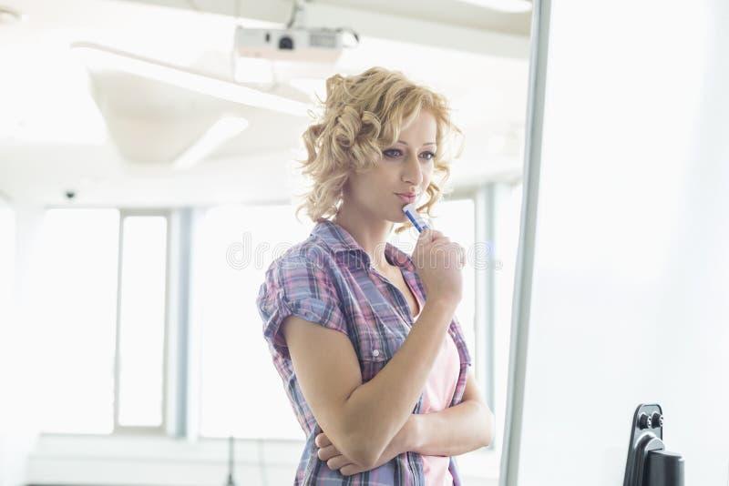 Koncentrerad affärskvinna som ser presentationsbrädet i idérikt kontor arkivfoto