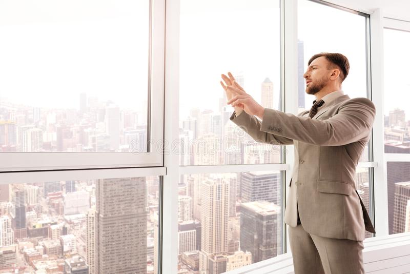 Koncentrerad affärsman som använder genomskinlig skärm i hans kontor royaltyfri foto