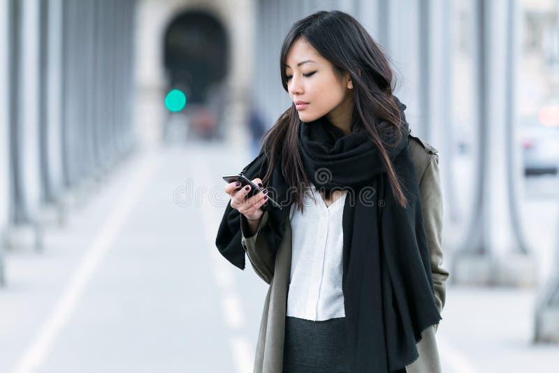 Koncentrerad asiatisk ung kvinna som använder hennes mobiltelefon i gatan royaltyfria foton