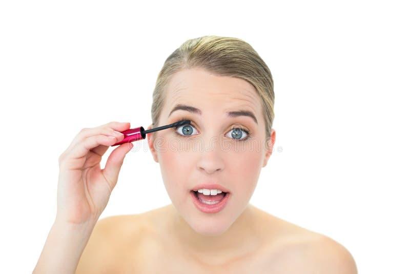 Koncentrerad attraktiv blondin som applicerar mascara arkivfoto
