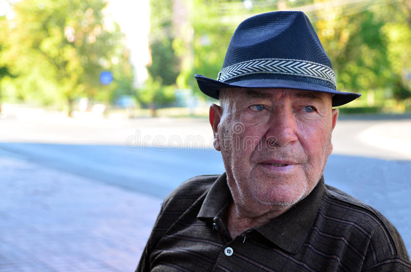 Koncentrerad bärande hatt för gamal man arkivfoton