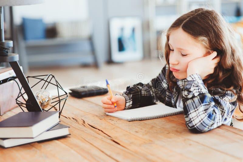 koncentrerad barnflicka som gör läxa Fundersam skolaunge som tänker och söker efter ett svar arkivfoto