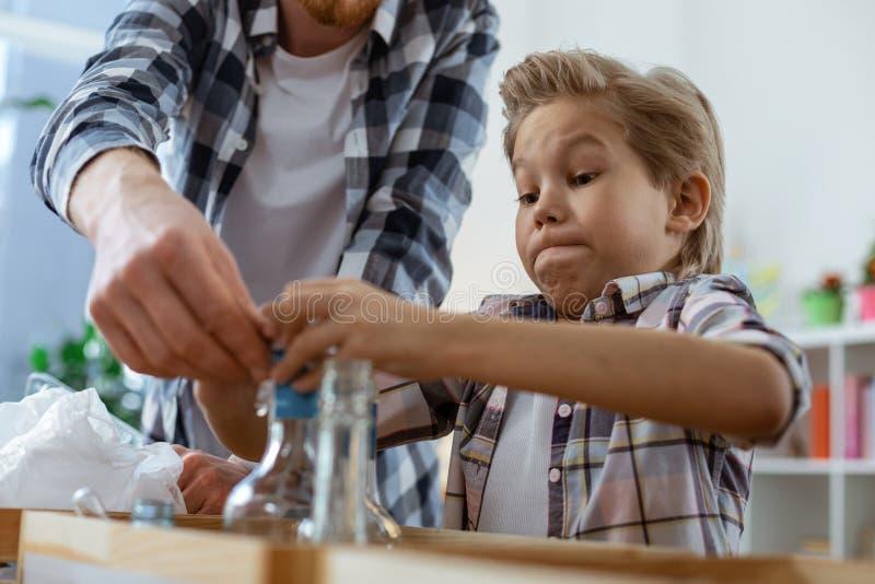 Koncentrerad blond ung pojke observera förehavanden av hans lärare royaltyfri fotografi