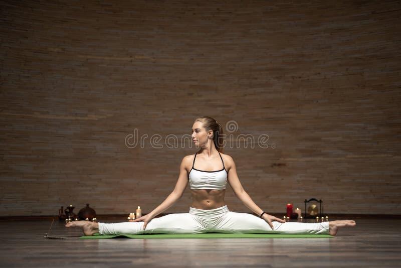 Koncentrerad dam som ifrån varandra delar ben och sträcker på matt yoga royaltyfria foton