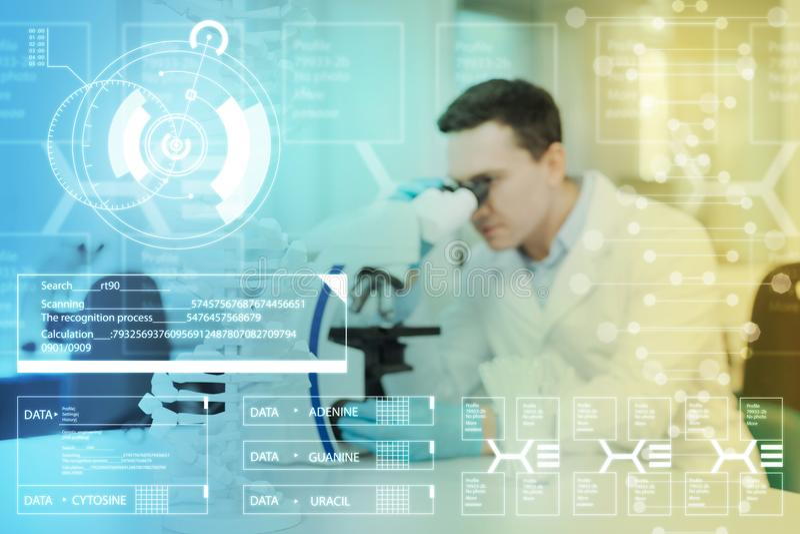 Koncentrerad doktor som använder det moderna mikroskopet, medan arbeta royaltyfri bild