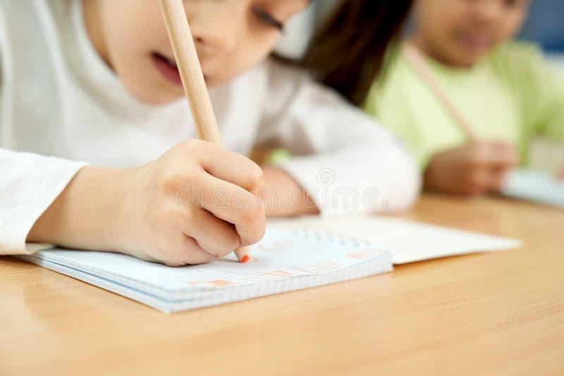 Koncentrerad flicka i process av handstil i anteckningsbok royaltyfri foto
