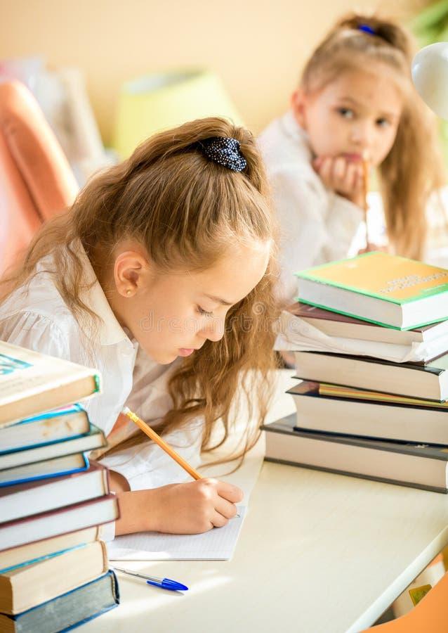 Koncentrerad flicka som gör läxa medan klasskompis som försöker att skriva arkivbild