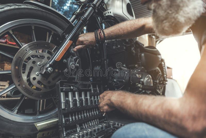 Koncentrerad gamal man som kontrollerar mopeden royaltyfri fotografi
