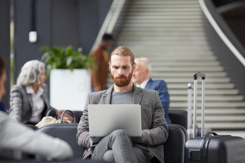 Koncentrerad grabb som arbetar i flygplats arkivbilder