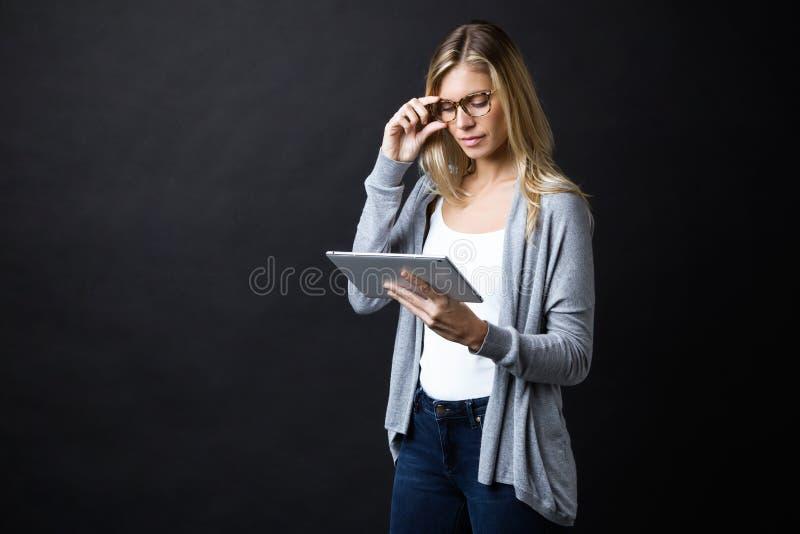 Koncentrerad härlig ung kvinna med glasögon som arbetar med den digitala minnestavlan, medan stå över svart bakgrund royaltyfri fotografi